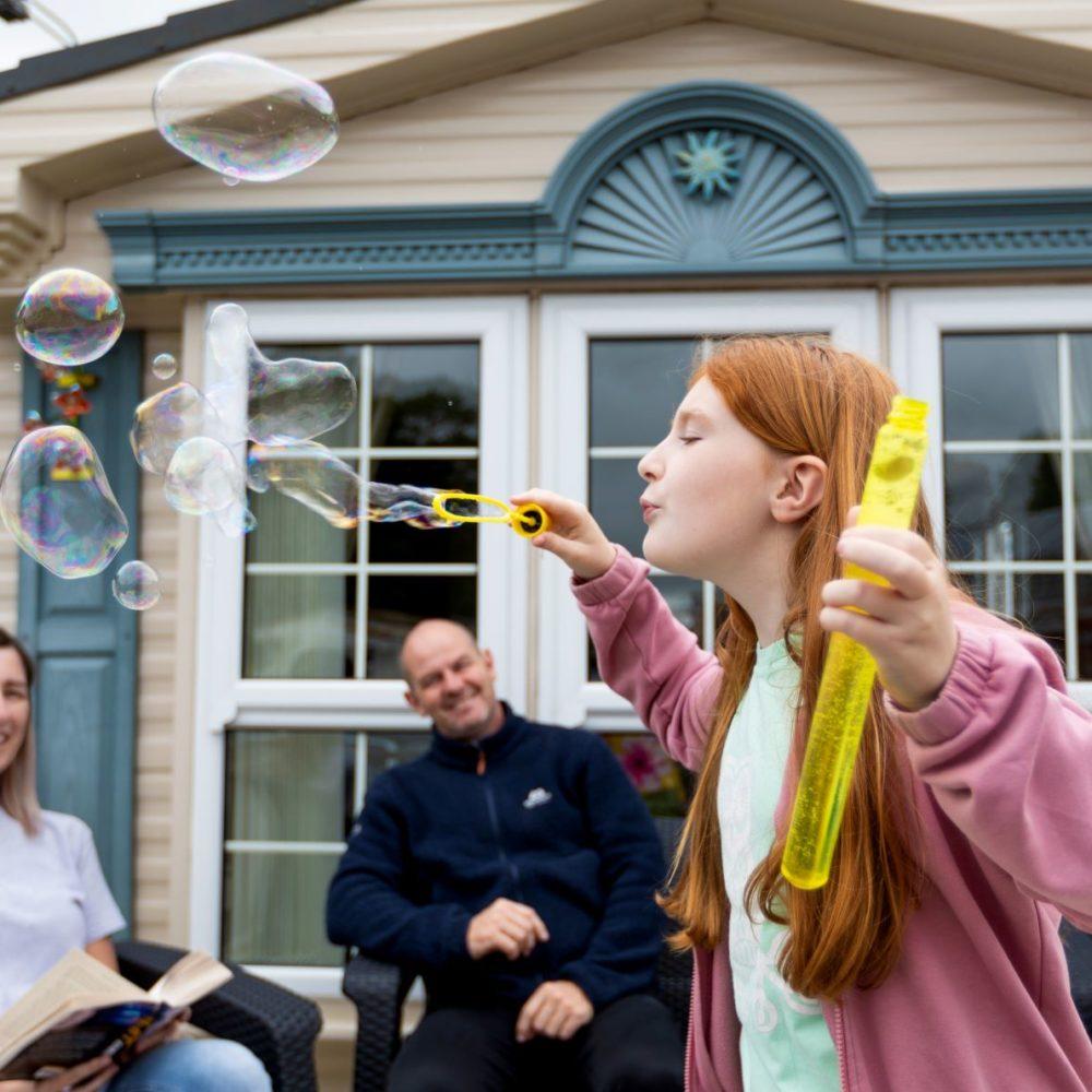 Girl blowing bubbles outside caravan park home near Lytham