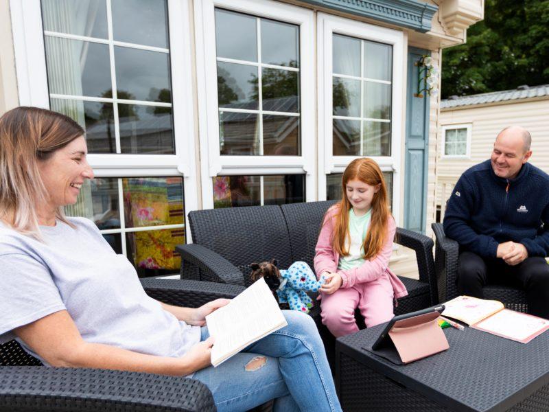 Family relaxing outside caravan park home
